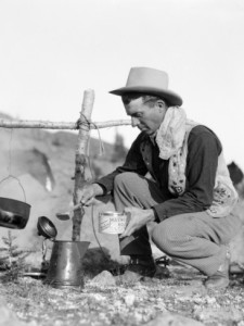 h-armstrong-roberts-cowboy-kneeling-by-campfire-pouring-coffee